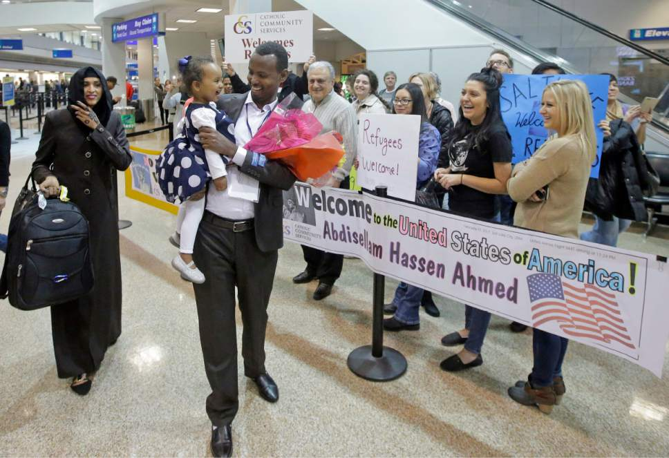 Abdisellam Hassen Ahmed, a Somali refugee who had been stuck in limbo after President Donald Trump temporarily banned refugee entries, walks with his wife Nimo Hashi, and his 2-year-old daughter, Taslim, after arriving at Salt Lake International Airport, Friday, Feb. 10, 2017, in Salt Lake City. Ahmed meet his daughter for the first time. Ahmed is among a wave of refugees around the country making belated arrivals after their trips were cancelled several weeks ago after Trump's executive order. (AP Photo/Rick Bowmer)