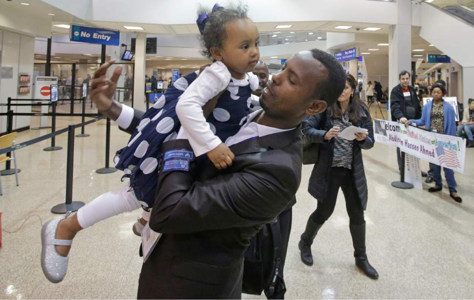 Abdisellam Hassen Ahmed, a Somali refugee who had been stuck in limbo after President Donald Trump temporarily banned refugee entries, holds his 2-year-old daughter, Taslim, after meeting her for the first time after arriving at Salt Lake International Airport, Friday, Feb. 10, 2017, in Salt Lake City. Ahmed is among a wave of refugees around the country making belated arrivals after their trips were cancelled several weeks ago after Trump's executive order. (AP Photo/Rick Bowmer)