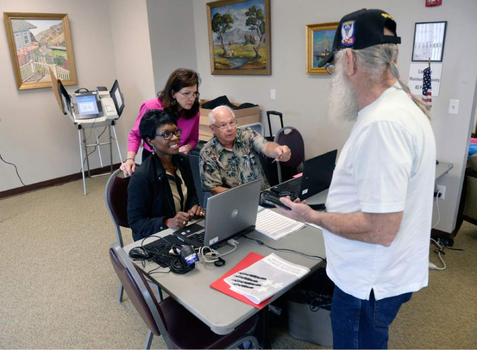 Al Hartmann  |  Tribune file photo Poll workers check in Army veteran Dail Sullivan at the River Bend Senior Center in Salt Lake City in October, with the start of early voting. A bill before the Legislature would extend early voting through the Monday before the election.