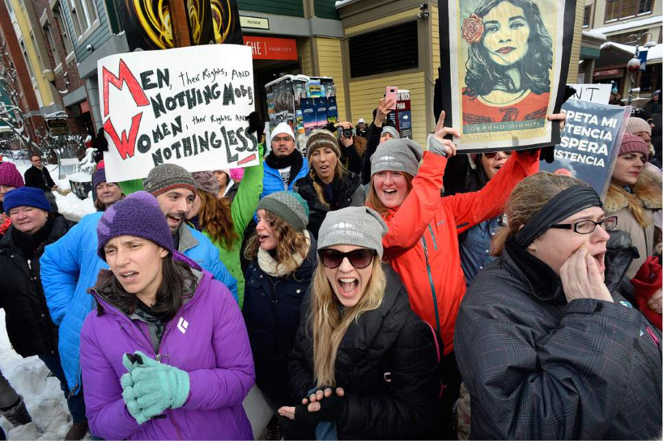 "Scott Sommerdorf   |  The Salt Lake Tribune   A group of Salt Lake City women, including Carrie Zumnarski, left, and Gabby Gabbitas center, and Allie Kessler, back right, holding the ""defend dignity"" sign, cheer at the end of the Women's March on Main Street in Park City on Saturday, Jan. 21, 2017."