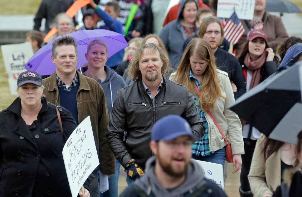 "Salt Lake Tribune reporter Nate Carlisle, left, interviews Kody Brown, center, from TV's reality show ""Sister Wives,"" as Brown marches during a protest at the state Capitol Friday, Feb. 10, 2017, in Salt Lake City. Several hundred people in polygamist relationships say they want Utah lawmakers and law enforcement officials to know that they're not going away and should be allowed the freedom to practice their plural marriages.  (AP Photo/Rick Bowmer)"