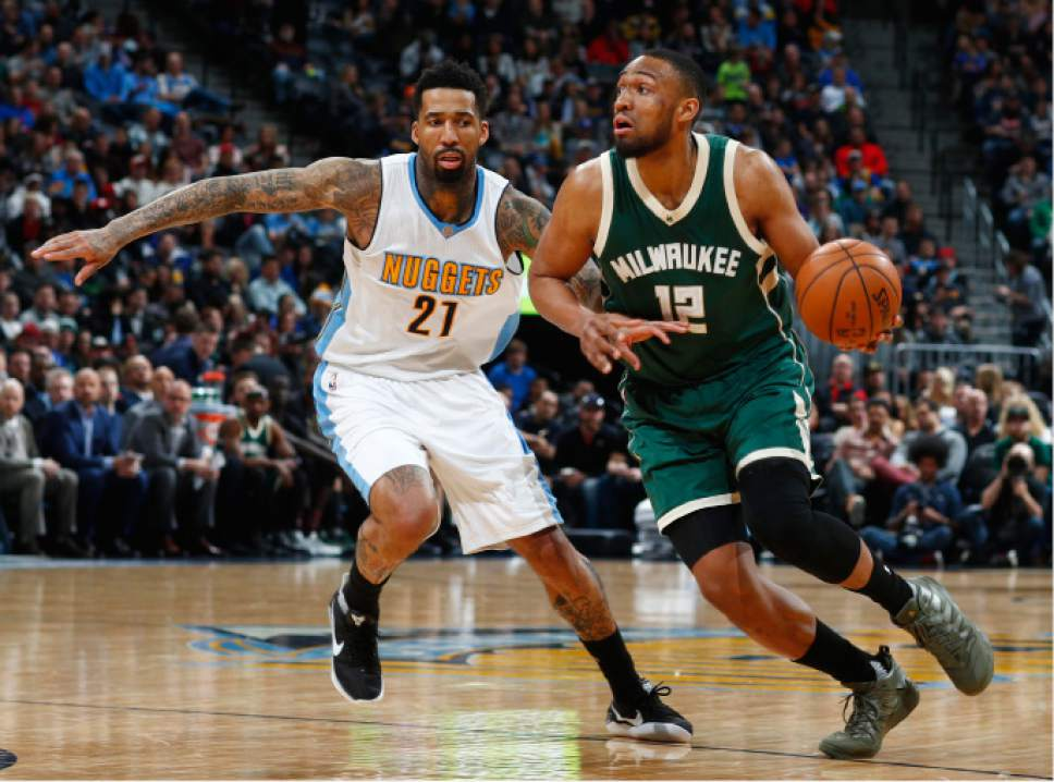 Milwaukee Bucks forward Jabari Parker, right, drives to the net past Denver Nuggets forward Wilson Chandler in the second half of an NBA basketball game Friday, Feb. 3, 2017, in Denver. The Nuggets won 121-117. (AP Photo/David Zalubowski)