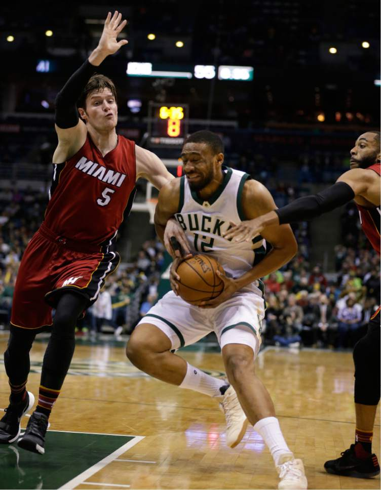 Milwaukee Bucks' Jabari Parker (12) grimaces as he drives against the Miami Heat's Luke Babbitt during the second half of an NBA basketball game Wednesday, Feb. 8, 2017, in Milwaukee. Parker was injured on the play and left the game. (AP Photo/Jeffrey Phelps)