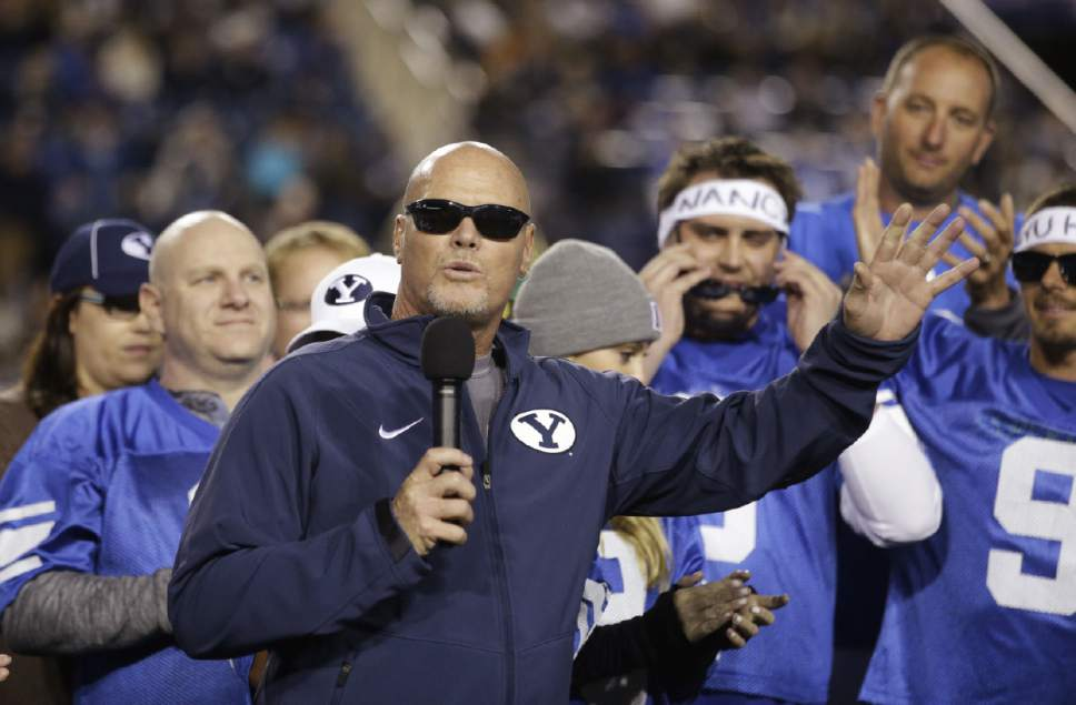 Former BYU and Chicago Bears quarterback Jim McMahon watches as his No. 9 jersey went on permanent display at LaVell Edwards Stadium, during BYU's NCAA college football game against Utah State on Friday, Oct. 3, 2014, in Provo, Utah.  (AP Photo/Rick Bowmer)
