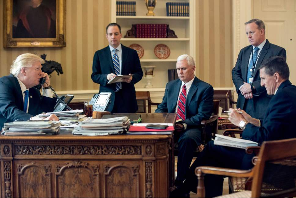 FILE - In this Jan. 28, 2017, file photo, President Donald Trump accompanied by, from second from left, Chief of Staff Reince Priebus, Vice President Mike Pence, White House press secretary Sean Spicer and National Security Adviser Michael Flynn speaks on the phone with Russian President Vladimir Putin in the Oval Office at the White House in Washington. Flynn resigned Monday, Feb. 13, 2017. (AP Photo/Andrew Harnik, File)