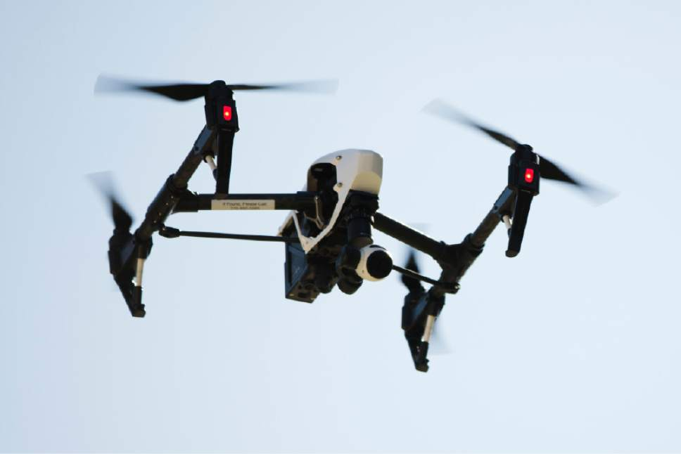 FILE - In this April 14, 2016 file photo, a drone captures videos and still images of an apartment building in Philadelphia. Federal aviation officials say so many people are registering drones and applying for drone pilot licenses, they wonder if there will eventually be millions of drones crowding the nation's skies.  (AP Photo/Matt Rourke, File)
