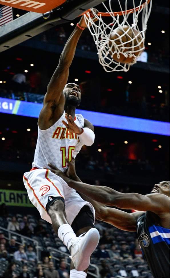 Atlanta Hawks guard Tim Hardaway Jr. (10) dunks over Orlando Magic center Bismack Biyombo during the first half of an NBA basketball game, Saturday, Feb. 4, 2017, in Atlanta. (AP Photo/John Amis)