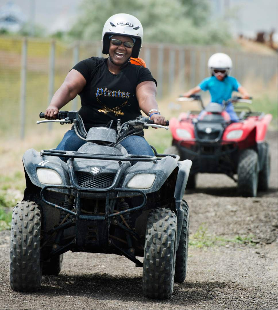 Rick Egan  |  The Salt Lake Tribune  Nakia Armstrong, Salt Lake, leads 8-year-old Skyler Salazar, as she she takes a spin on an ATV for the first time in her life, during Outdoor Adventure Days at the Lee Kay Public Shooting Range in Salt Lake City on Friday, June 10, 2016. The free event continues Saturday with fishing, kayaking and paddleboarding, and archery and firearms instruction.