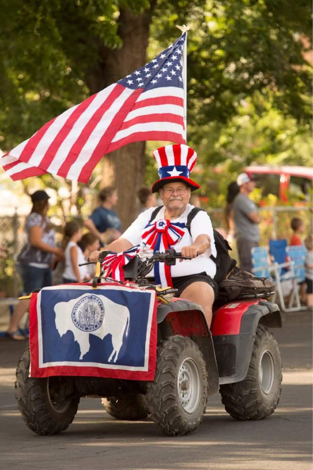 "Rick Egan  |  The Salt Lake Tribune  Bruce ""Buffalo"" Fuller rides his ATV down Main Street, in the Hurricane Independence day parade, Friday, July 4, 2014"