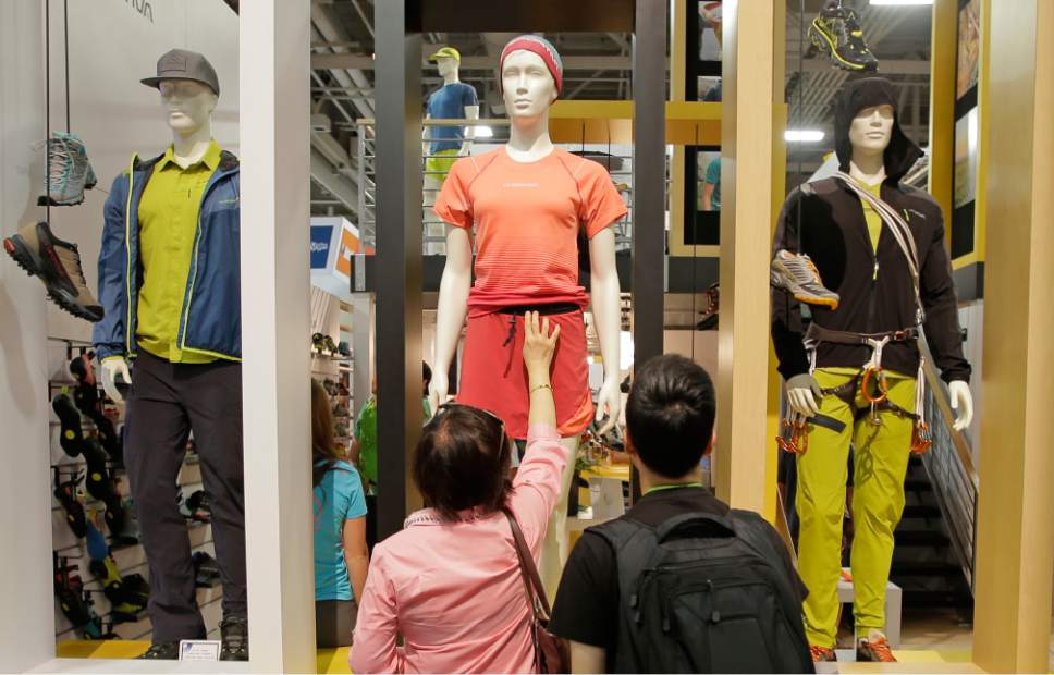 A woman reaches to touch the fabric on a mannequin at the La Sportiva booth during the Outdoor Retailer show Friday, Aug. 5, 2016, in Salt Lake City. A wide array of clothing, gear and equipment specifically designed for women outdoor adventurers is on display at the summer version of the world's largest outdoor gear show for retailers that brings thousands of people to Salt Lake City. (AP Photo/Rick Bowmer)