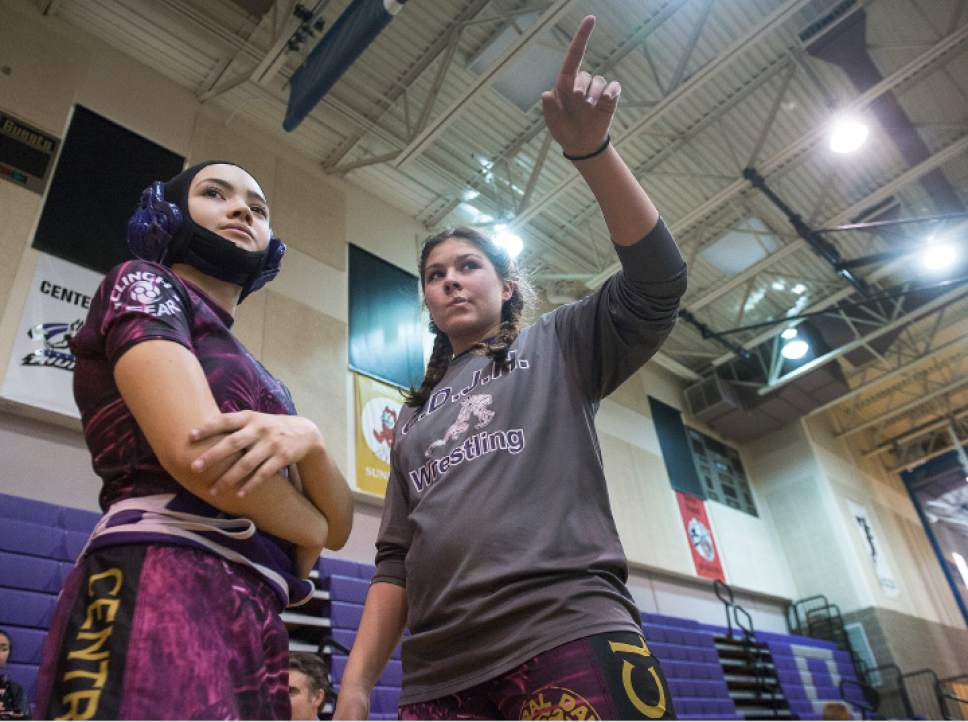 Leah Hogsten  |  The Salt Lake Tribune l-r Central Davis Junior High wrestler Gabi Serrao, 14, gets advice from teammate Kathleen Janis, 15, before hitting the mat February 14, 2017 against her Mueller Park Junior High opponent. Janis' family has sued the Davis County School District to allow her to wrestle for her school and a judge has temporarily ruled in her favor, allowing her to  compete with the team.
