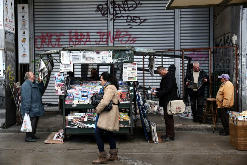 People read newspapers around a kiosk in Athens, Tuesday, Feb. 21, 2017. Greece and its European creditors agreed Monday to resume talks on what economic reforms the country must make next in order to get the money it needs to avoid bankruptcy and a potential exit from the euro this summer. (AP Photo/Yorgos Karahalis)