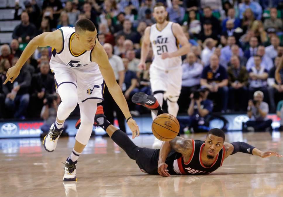 Portland Trail Blazers guard Damian Lillard, right, falls as Utah Jazz guard Dante Exum (11) reaches for a loose ball during the second half of an NBA basketball game Wednesday, Feb. 15, 2017, in Salt Lake City. The Jazz won 111-88. (AP Photo/Rick Bowmer)