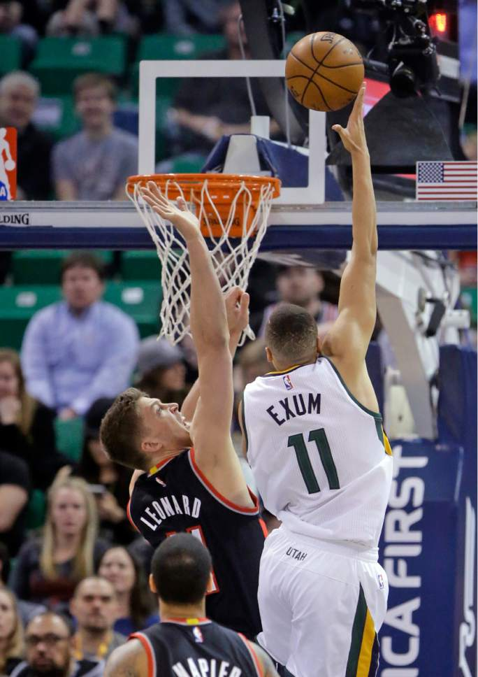 Utah Jazz guard Dante Exum (11) lays the ball as Portland Trail Blazers forward Meyers Leonard, left, defends during the first half of an NBA basketball game Wednesday, Feb. 15, 2017, in Salt Lake City. (AP Photo/Rick Bowmer)