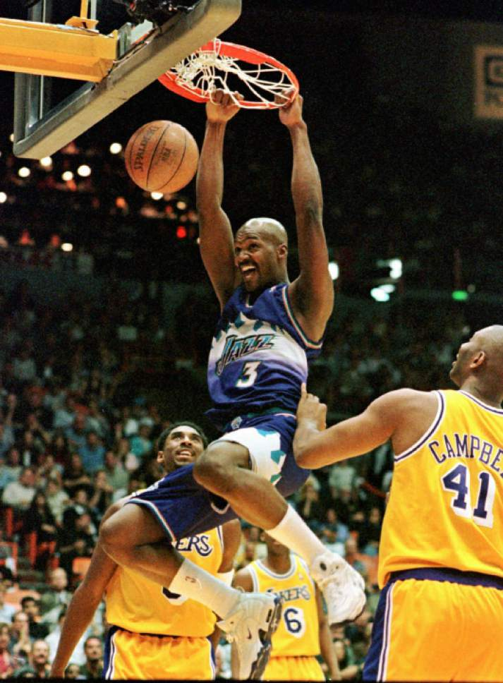Utah Jazz' Bryon Russell dunks as Los Angeles Lakers' Kobe Bryant, left, and Elden Campbell look on during the first half of their semi-final playoff game, Friday night, May 22, 1998, in Inglewood, Calif. (AP Photo/Mark J. Terrill)