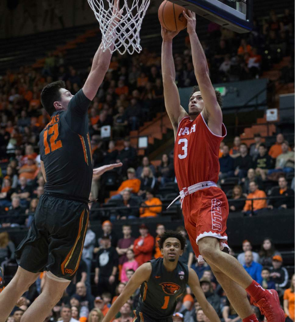 Oregon State's Drew Eubanks (12) contests the shot of Utah's Devon Daniels (3) during the first half of an NCAA college basketball game in Corvallis, Ore., Sunday, Feb. 19, 2017. (AP Photo/Timothy J. Gonzalez)