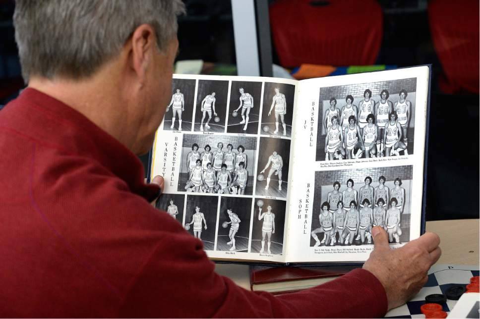 Scott Sommerdorf   |  The Salt Lake Tribune   University of Utah athletic director Chris Hill looks through a yearbook from his time at Granger High School, Thursday, February 9, 2017. Early in his career, Hill spent four years at Granger High as a math teacher and basketball coach.