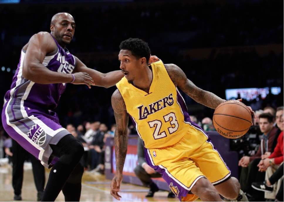 Los Angeles Lakers' Lou Williams, right, drives past Sacramento Kings' Anthony Tolliver during the first half of an NBA basketball game, Tuesday, Feb. 14, 2017, in Los Angeles. (AP Photo/Jae C. Hong)