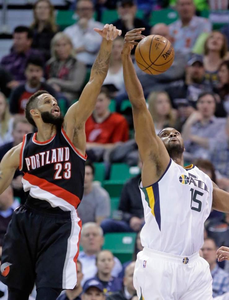 Utah Jazz forward Derrick Favors (15) wins a rebound from Portland Trail Blazers guard Allen Crabbe (23) during the first half of an NBA basketball game Wednesday, Feb. 15, 2017, in Salt Lake City. (AP Photo/Rick Bowmer)