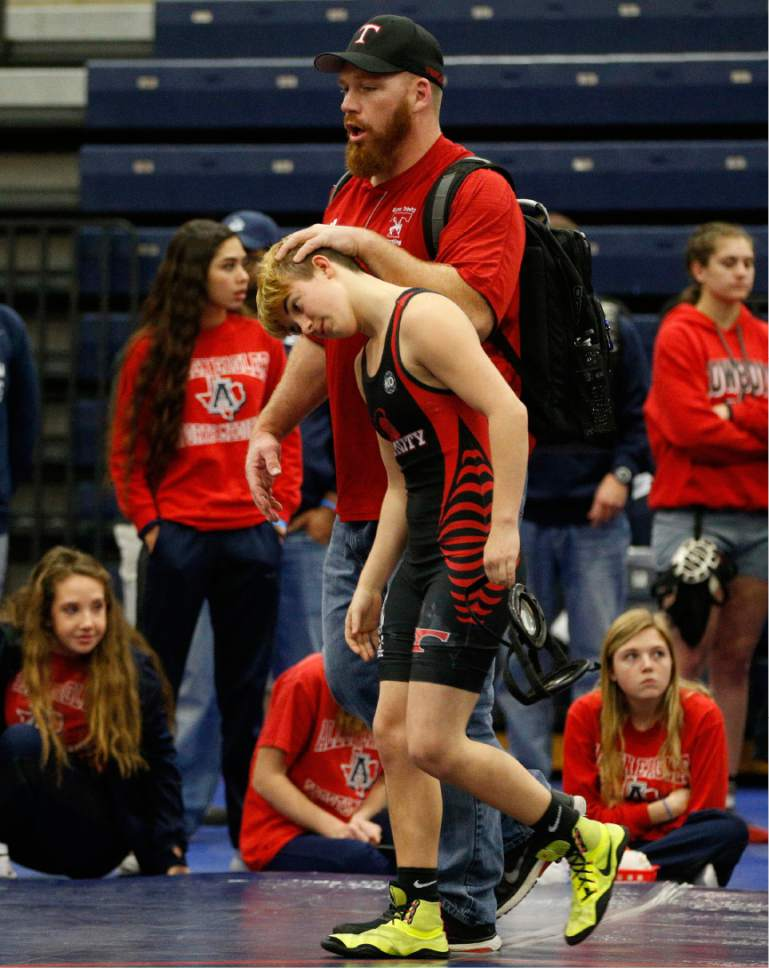 In this Feb. 18, 2017 photo, Euless Trinity's Mack Beggs is consoled by coach Travis Clark after Beggs' opponent forfeited during the finals of the UIL Region 2-6A wrestling tournament at Allen High School in Allen, Texas.  Beggs, who is transgender, is transitioning from female to male, won the girls regional championship.  (Nathan Hunsinger/The Dallas Morning News via AP)