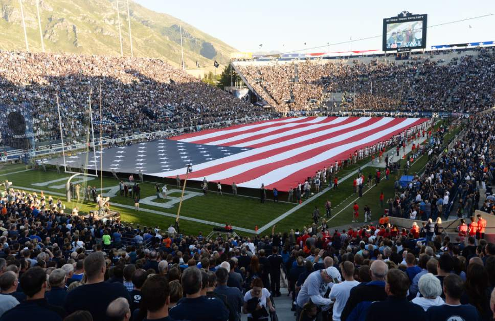 Steve Griffin  |  The Salt Lake Tribune A giant American Flag is held by BYU Army and Air Force ROTC members as well as the BYU and Houston football players on Sept. 11, 2014, in honor of the anniversary of 9/11 before the start of the game between BYU and Houston and LaVell Edwards Stadium in Provo.