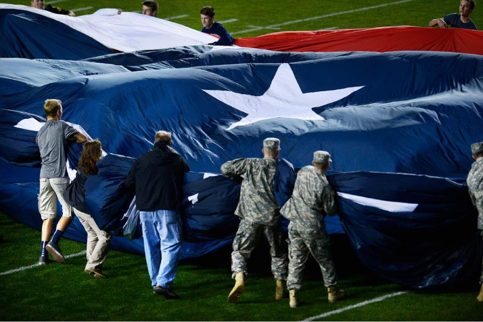 Scott Sommerdorf   |  The Salt Lake Tribune BYU ROTC members struggle to gather up the huge American flag used for the national anthem prior to the kickoff between UCONN and BYU, October 2, 2015.