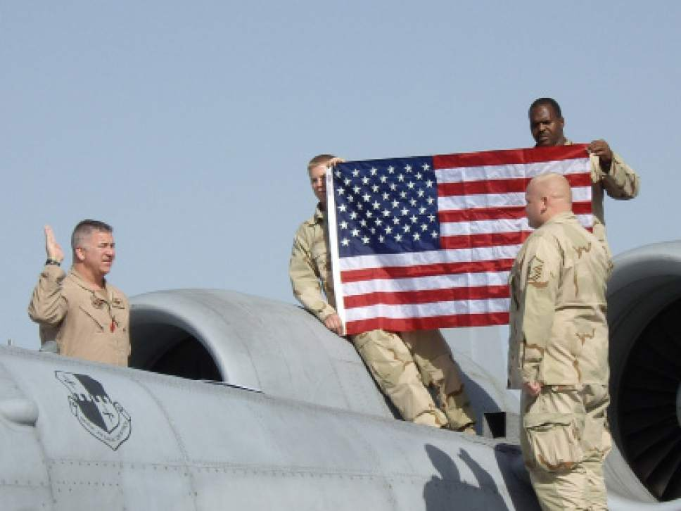 |  Courtesy of U.S. Air Force  BAGRAM AIR BASE, Afghanistan – Lt. Col. Timothy Hogan re-enlists Master Sgt. Brian Downer on the wing of an A-10 as Senior Airman Calvin Woody and Staff Sgt. Victor Latson hold a flag in the background April 1, 2008. The Airmen are all deployed from Spangdahlem Air Base, Germany.