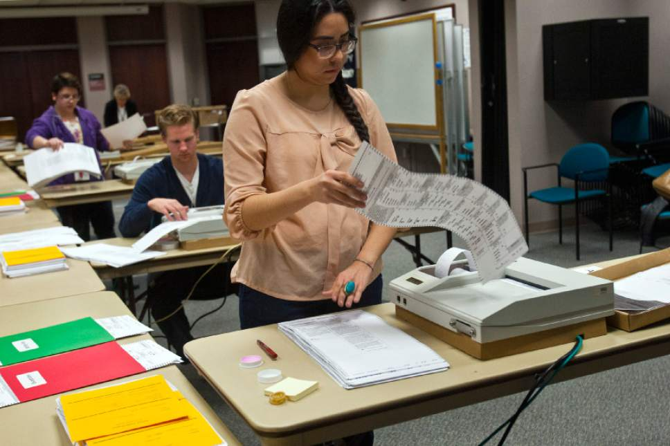 Chris Detrick  |  Tribune file photo Gracie Velasquez scans ballots at the Salt Lake County clerk's office in a past election. Vote-by-mail is expected to handle most balloting in this year's primary and general election.
