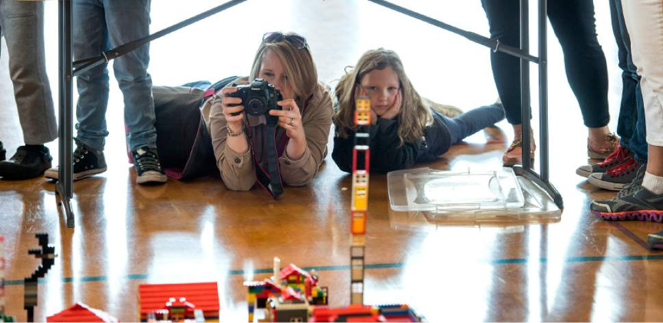 Leah Hogsten  |  The Salt Lake Tribune l-r Katie Spencer snaps photos of the LEGO city after her daughter Avery, 7, and her two other children built their own additions. Over 800 kids sorted through 50,000 pieces of LEGOs to make additions to the Salt Lake Valley out of LEGO in the hopes of getting kids interested in engineering and other STEM and STEAM-related fields at the Gene Fullmer Recreation Center, February 25, 2017.