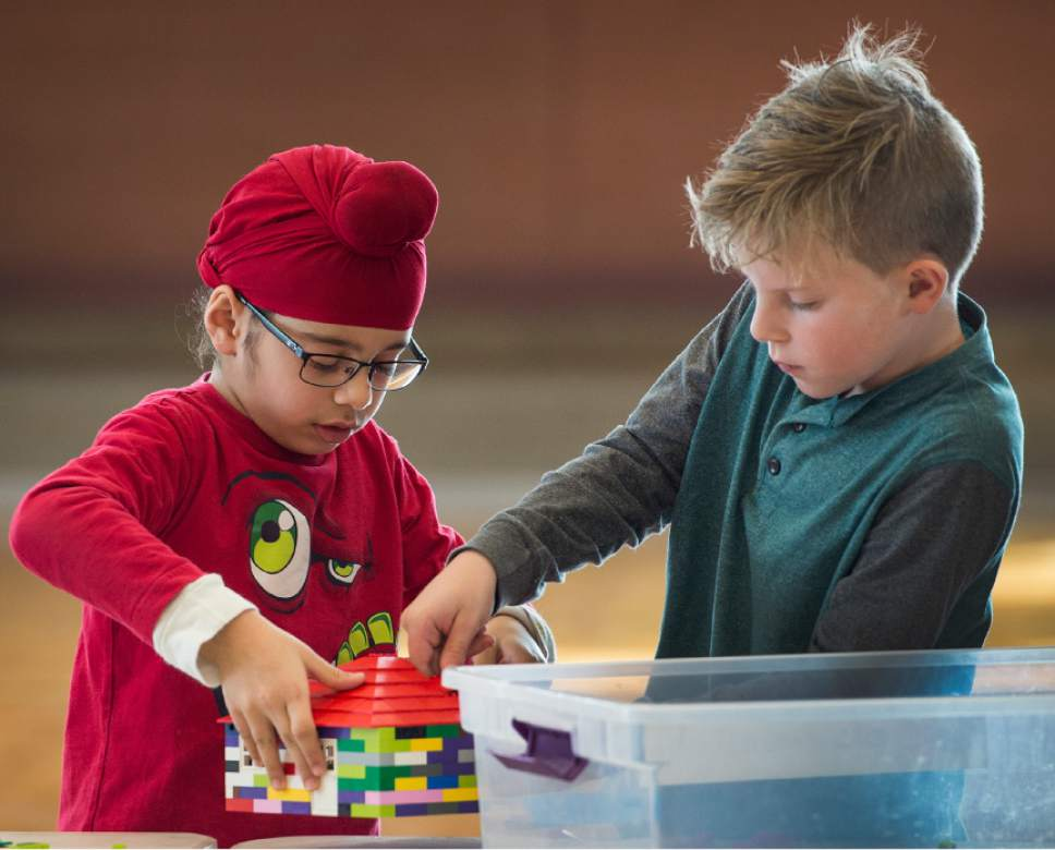 Leah Hogsten  |  The Salt Lake Tribune Furmaan Tib, 6, left, and Colin Corbett, 9, use teamwork to put the finishing touches on a house they built together. Over 800 kids sorted through 50,000 pieces of LEGOs to make additions to the Salt Lake Valley out of LEGO in the hopes of getting kids interested in engineering and other STEM and STEAM-related fields at the Gene Fullmer Recreation Center on Saturday.