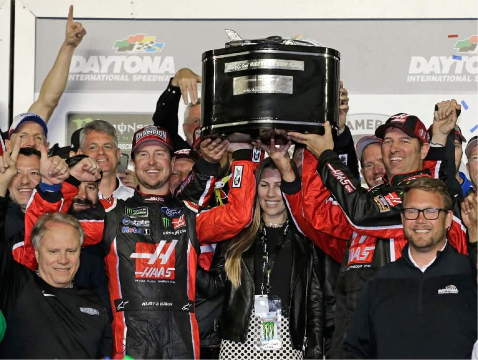 Kurt Busch, center left, and team members raise the trophy in Victory Lane after winning the NASCAR Daytona 500 auto race at Daytona International Speedway in Daytona Beach, Fla., Sunday, Feb. 26, 2017. (AP Photo/Terry Renna)