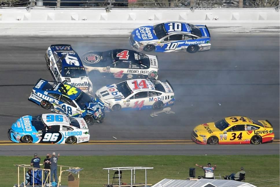 Jimmie Johnson (48), Clint Bowyer (14), Chris Buescher (37), Kevin Harvick (4), D.J. Kennington (96) and Danica Patrick (10) collide in a multi-car wreck between Turns 3 and 4, as Landon Cassill (34) drives past, during the NASCAR Daytona 500 auto race at Daytona International Speedway, Sunday, Feb. 26, 2017, in Daytona Beach, Fla. (AP Photo/Phelan M. Ebenhack)