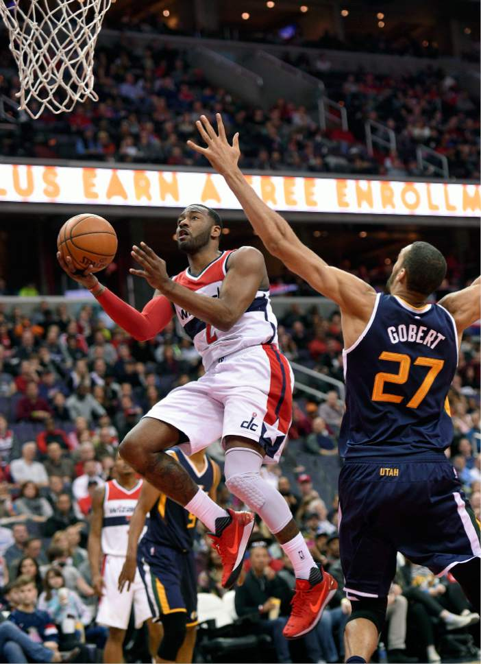 Washington Wizards guard John Wall (2) goes to the basket against Utah Jazz center Rudy Gobert (27), of France, during the first half of an NBA basketball game, Sunday, Feb. 26, 2017, in Washington. (AP Photo/Nick Wass)
