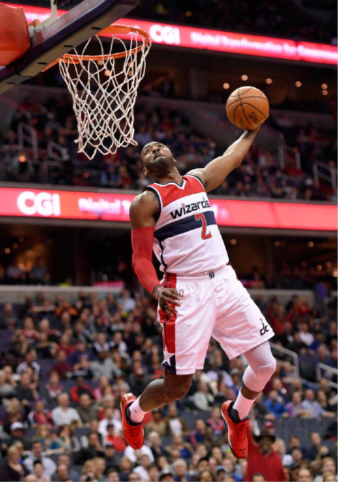 Washington Wizards guard John Wall (2) goes for a dunk during the first half of an NBA basketball game against the Utah Jazz, Sunday, Feb. 26, 2017, in Washington. (AP Photo/Nick Wass)
