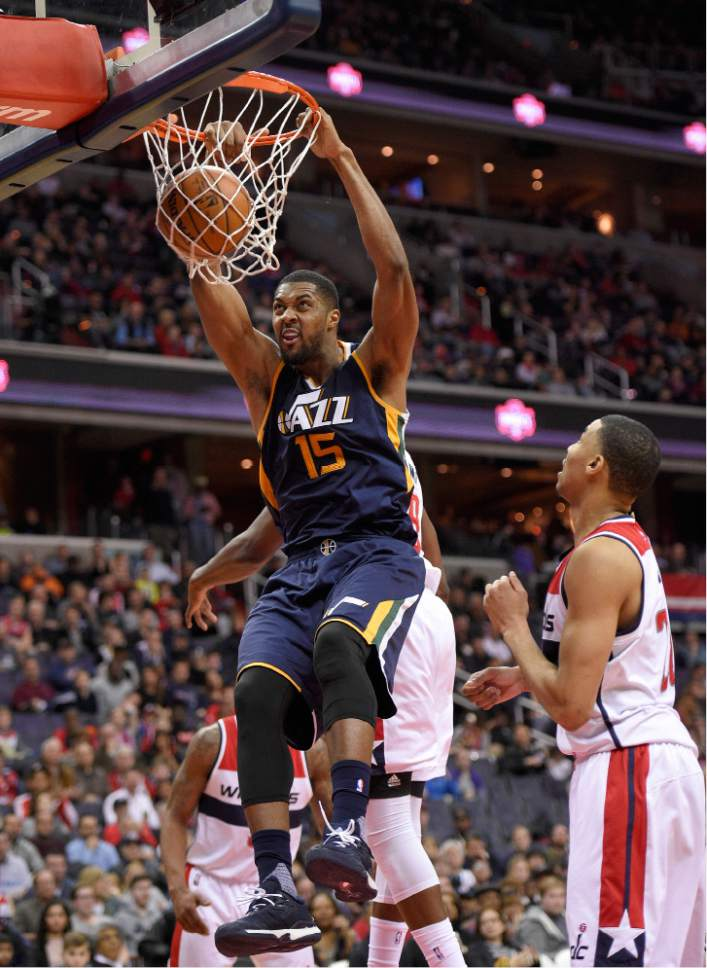 Utah Jazz forward Derrick Favors (15) dunks against Washington Wizards forward Otto Porter Jr., right, during the second half of an NBA basketball game, Sunday, Feb. 26, 2017, in Washington. The Jazz won 102-92. (AP Photo/Nick Wass)