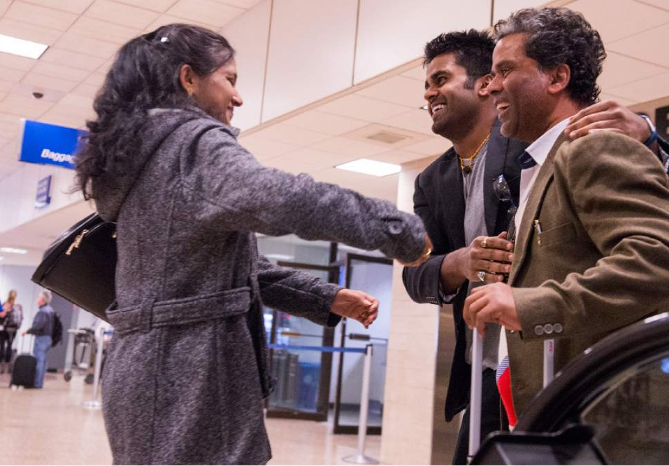 Leah Hogsten  |  The Salt Lake Tribune l-r Sarita Sah greets her husband Ken for the first time in over three weeks since she left India. Kunal Sah, 23, welcomes his father, Ken Sah, back to the U.S. for the first time in over 10 years at the Salt Lake International Airport. Kunal's parents, Ken and Sarita Sah, were forced to leave the country after losing their legal battle with U.S. Immigration authorities. Kunal has been running the family's hotel business in Green River since 2011, trying to keep his parents' dream alive without them.