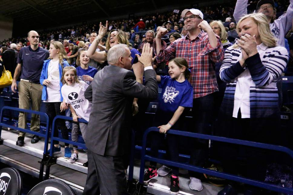 BYU coach Dave Rose, center, celebrates with fans after BYU defeated No. 1 Gonzaga 79-71 in an NCAA college basketball game in Spokane, Wash., Saturday, Feb. 25, 2017. (AP Photo/Young Kwak)