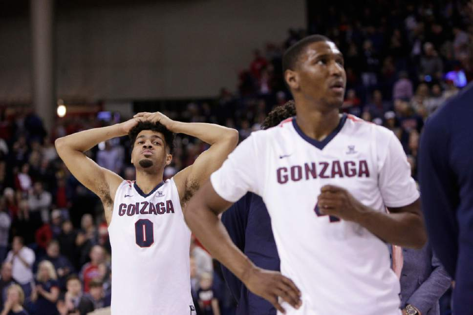 Gonzaga guards Silas Melson (0) and Jordan Mathews (4) stand on the court during senior night speeches after Gonzaga's 79-71 loss to BYU in an NCAA college basketball game in Spokane, Wash., Saturday, Feb. 25, 2017. (AP Photo/Young Kwak)