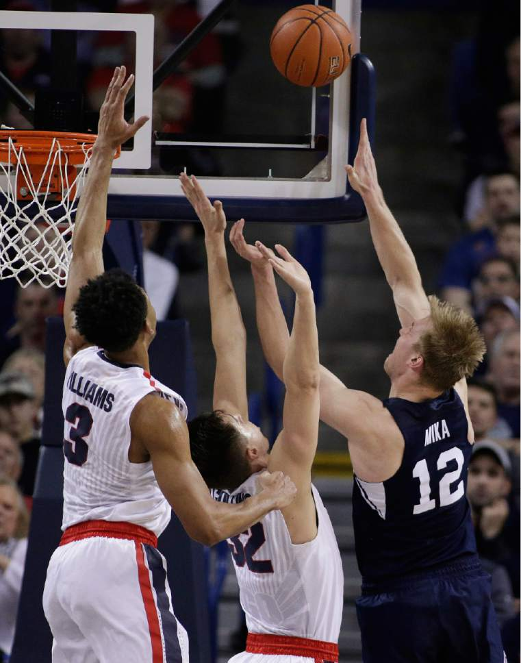 BYU forward Eric Mika (12) shoots against Gonzaga forwards Zach Collins (32) and Johnathan Williams (3) during the second half of an NCAA college basketball game in Spokane, Wash., Saturday, Feb. 25, 2017. BYU won 79-71. (AP Photo/Young Kwak)