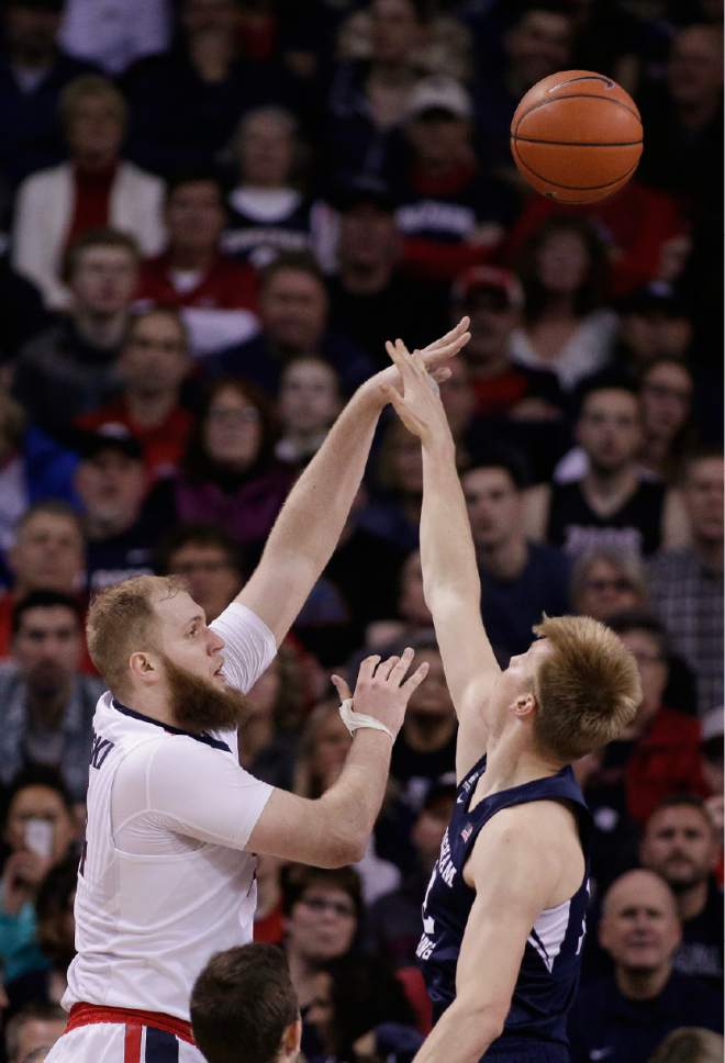 Gonzaga center Przemek Karnowski, left, shoots against BYU forward Eric Mika during the first half of an NCAA college basketball game in Spokane, Wash., Saturday, Feb. 25, 2017. (AP Photo/Young Kwak)