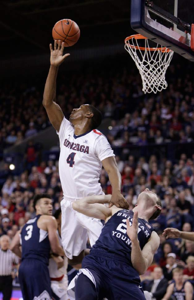 Gonzaga guard Jordan Mathews (4) and BYU forward Davin Guinn go after the ball during the first half of an NCAA college basketball game in Spokane, Wash., Saturday, Feb. 25, 2017. (AP Photo/Young Kwak)