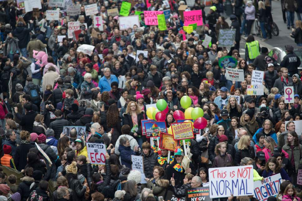 Demonstrators march across 42nd Street during a women's march, Saturday, Jan. 21, 2017, in New York. The march is being held in solidarity with similar events taking place in Washington and around the nation. (AP Photo/Mary Altaffer)