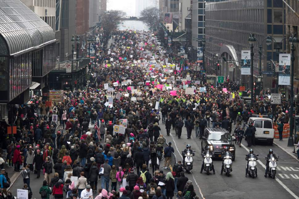 New York City police officers lead the demonstrators as they march across 42nd Street during a women's march in New York, Saturday, Jan. 21, 2017. The march is being held in solidarity with similar events taking place in Washington and around the nation. (AP Photo/Mary Altaffer)
