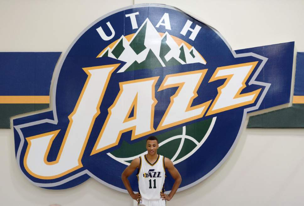 Steve Griffin  |  The Salt Lake Tribune   Jazz rookie Dante Exum stands below a giant Jazz logo during Jazz Media Day at the Zions Bank Basketball Center in Salt Lake City, Monday, September 29, 2014.