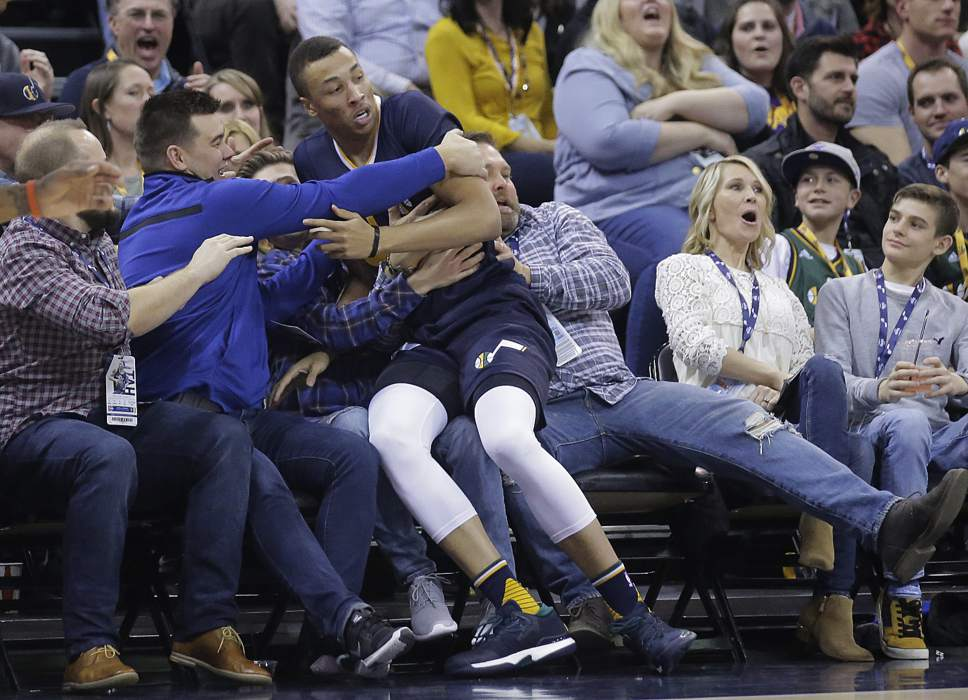 Utah Jazz guard Dante Exum falls into the crowd during the first half of the team's NBA basketball game against the Detroit Pistons Friday, Jan. 13, 2017, in Salt Lake City. (AP Photo/Rick Bowmer)