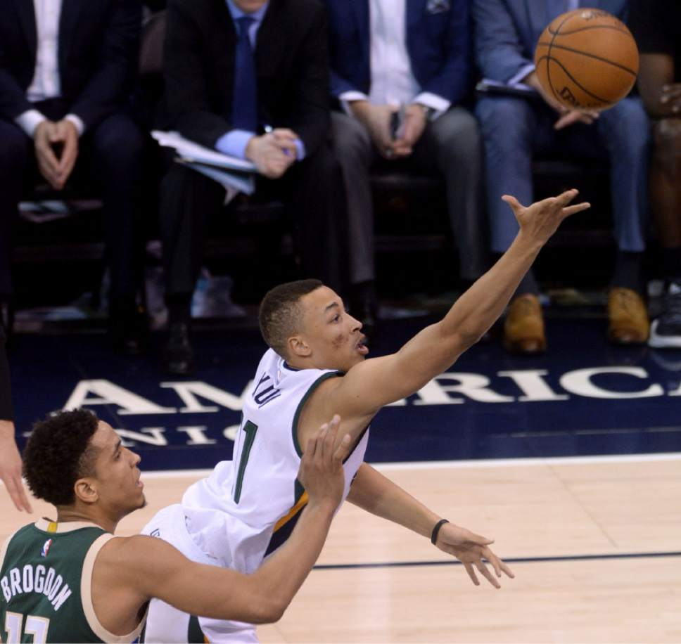 Steve Griffin / The Salt Lake Tribune  Utah Jazz guard Dante Exum (11) scoops up a shot as he gets by Milwaukee Bucks guard Malcolm Brogdon (13) during NBA game at Vivint Smart Home Arena in Salt Lake City Wednesday February 1, 2017.