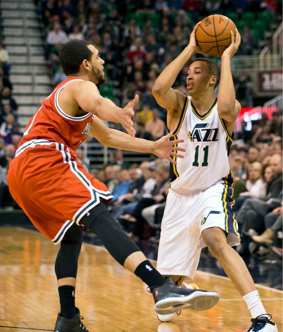 Lennie Mahler  |  The Salt Lake Tribune  Dante Exum looks to pass around Tyler Ennis in the first half of an NBA basketball game between the Utah Jazz and the Milwaukee Bucks at EnergySolutions Arena in Salt Lake City, Saturday, Feb. 28, 2015.