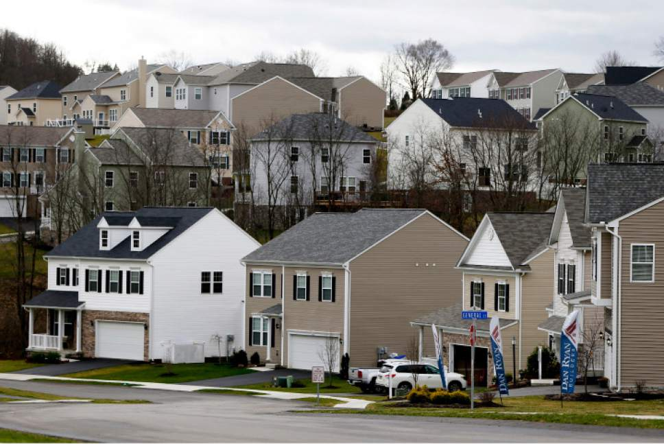 In this Wednesday, March 1, 2017, photo, a model home is open, at lower right, for potential buyers of either new construction or newly-built homes in a housing development, in Zelienople, Pa. Long-term U.S. mortgage rates fell during the week, breaking a holding pattern that prevailed for more than a month, according to information released Thursday by mortgage buyer Freddie Mac. (AP Photo/Keith Srakocic)