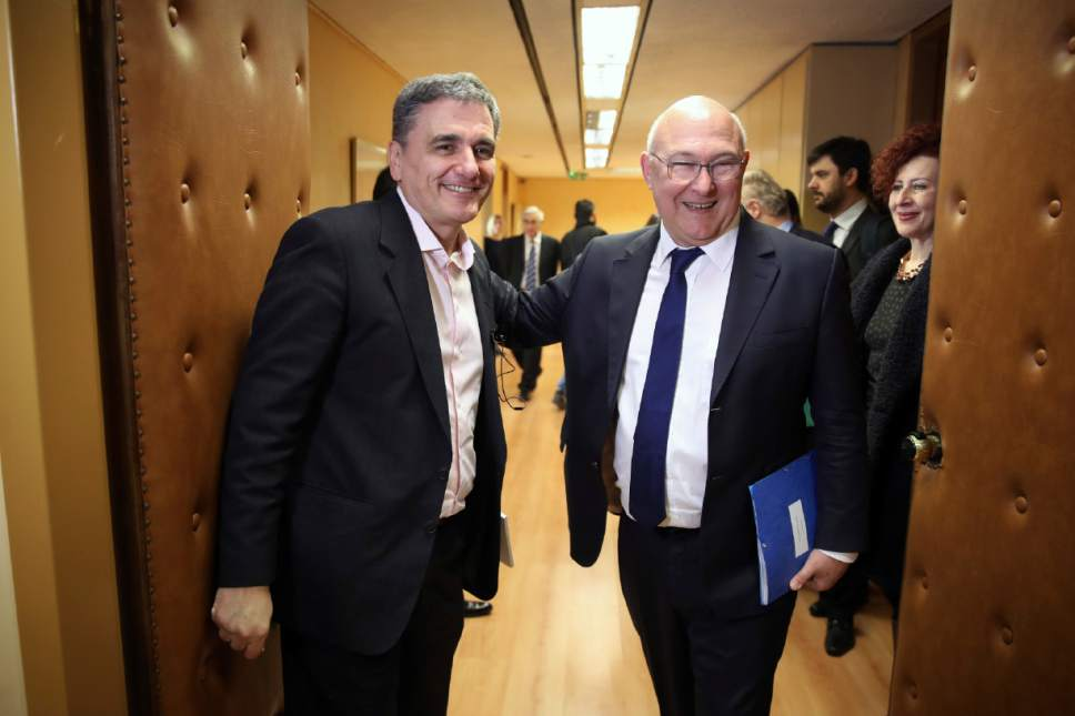 Greek Finance Minister Euclid Tsakalotos, left, and his French counterpart Michel Sapin smile before their meeting in Athens, Friday, March 3, 2017. Sapin escorts the French Prime Minister on his one-day visit in Athens as representatives from Greece's bailout inspectors in Europe and the International Monetary Fund have resumed talks with the Greek government on further reforms. (AP Photo/Yorgos Karahalis)