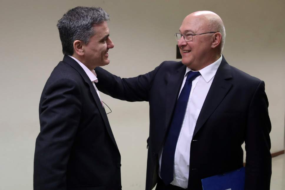 Greek Finance Minister Euclid Tsakalotos, left, welcomes his French counterpart Michel Sapin in Athens, Friday, March 3, 2017. Sapin escorts the French Prime Minister on his one-day visit in Athens as representatives from Greece's bailout inspectors in Europe and the International Monetary Fund have resumed talks with the Greek government on further reforms. (AP Photo/Yorgos Karahalis)